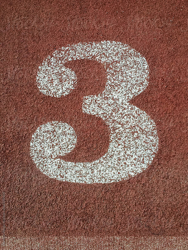 white number three painted on an running track by German Parga for Stocksy United