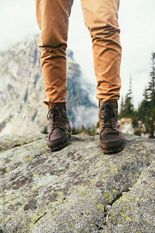Man In Brown Leather Boots Standing On Rock Surrounded By Mountains by Luke Mattson for Stocksy United
