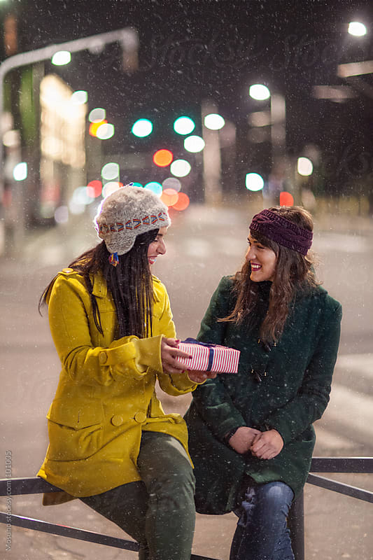 Friends Exchanging Presents on a Snowy Night by Mosuno for Stocksy United