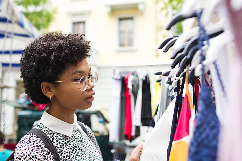 Young woman looking clothes at the market place by michela ravasio for Stocksy United