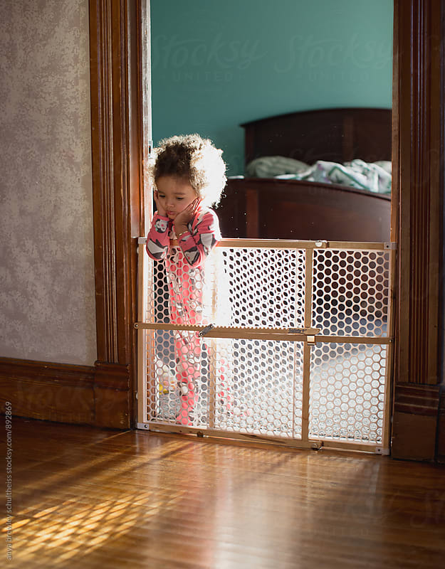 Portrait of toddler girl with curly hair standing behind a safety gate confining her to her bedroom by anya brewley schultheiss for Stocksy United
