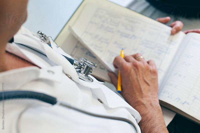 Doctor making notes on a patient folder by Borislav Zhuykov for Stocksy United
