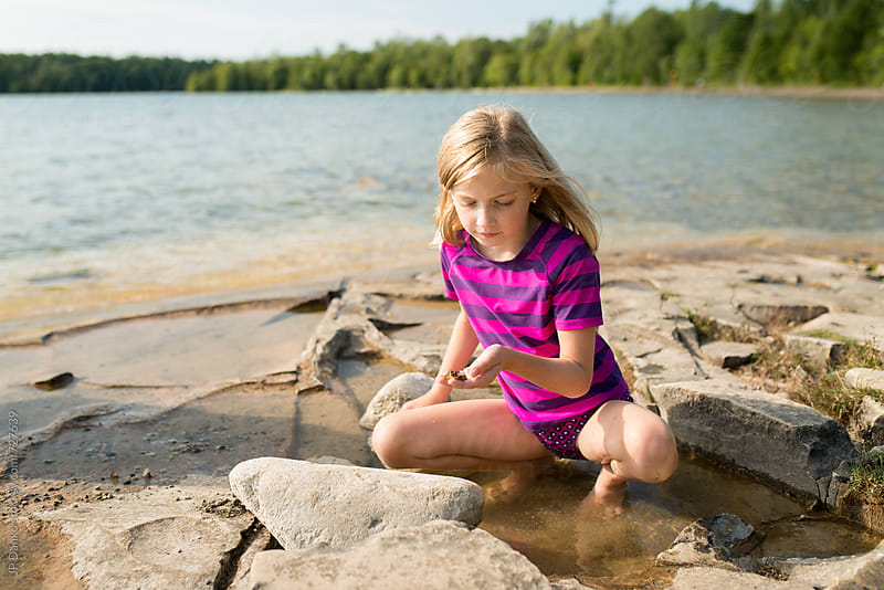 Little Girl Catching Frogs on a Rocky Northern Cottage Lakeshore on Warm Sunny Summer Day by JP Danko for Stocksy United