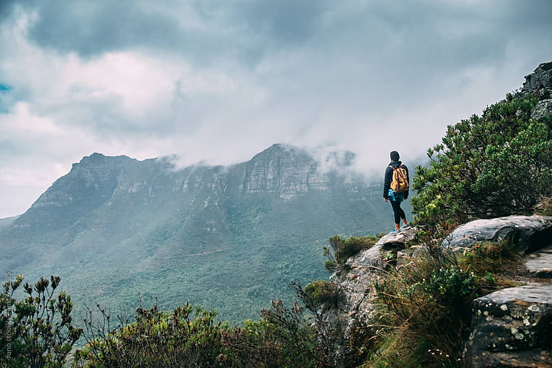 Female hiker on a rocky outcrop looking at the view on a stormy day by Micky Wiswedel for Stocksy United