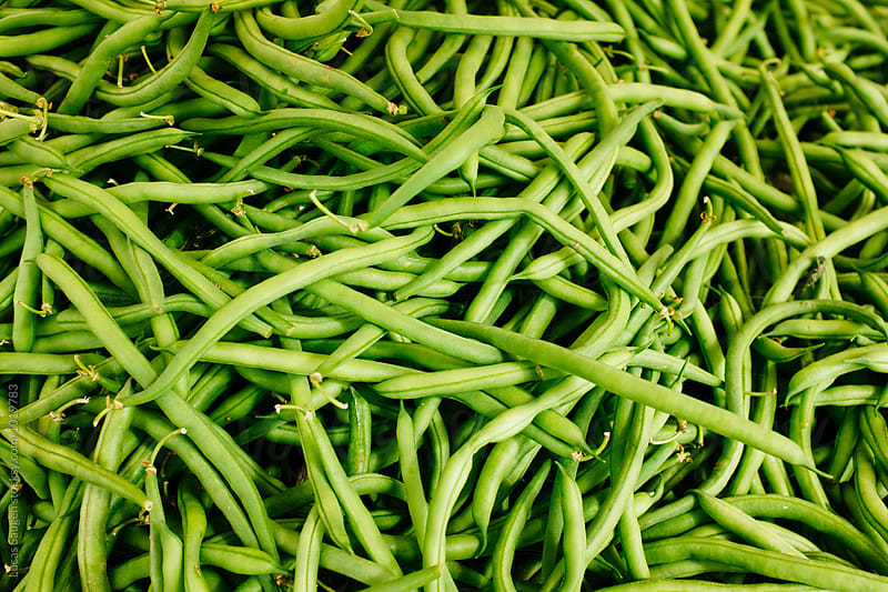 A stack of green beans at a local farmer's market. by Lucas Saugen for Stocksy United