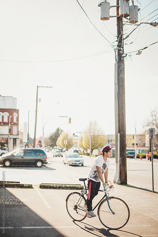 Teen boy riding bike downtown by Rob and Julia Campbell for Stocksy United