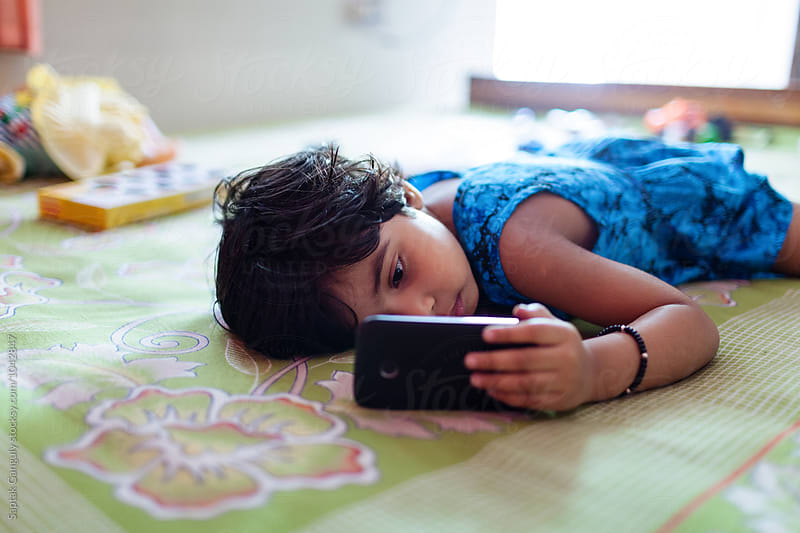 Little girl busy with mobile phone by Saptak Ganguly for Stocksy United