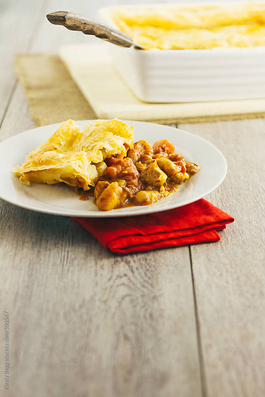 Chicken pie on plate with copy space in foreground by Kirsty Begg for Stocksy United