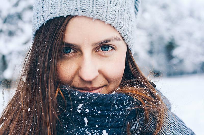 Young woman wearing knit hat in snowy field by Borislav Zhuykov for Stocksy United
