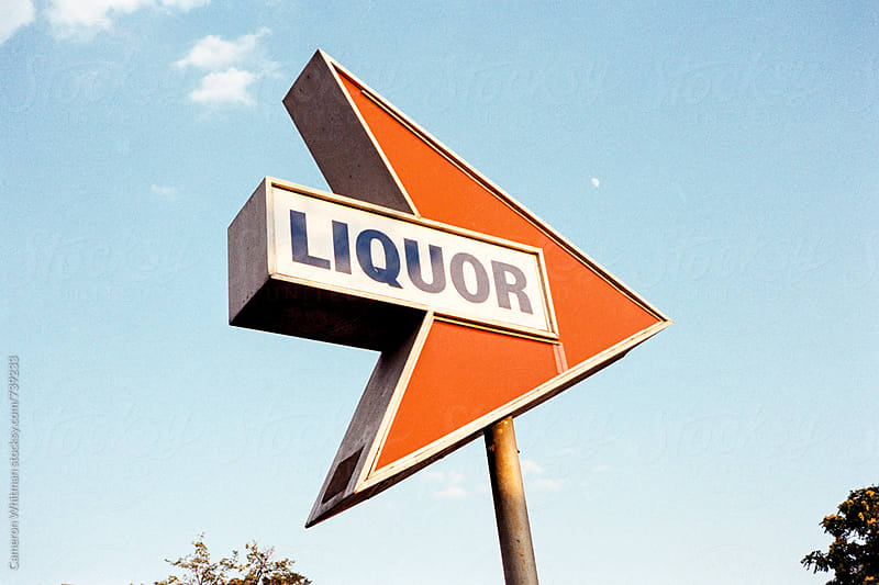 Arrow sign pointing towards an anonymous liquor store by Cameron Whitman for Stocksy United