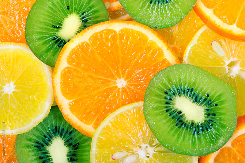 Fruit slices background (lemon, kiwi, orange, tangerine) by Ilya for Stocksy United