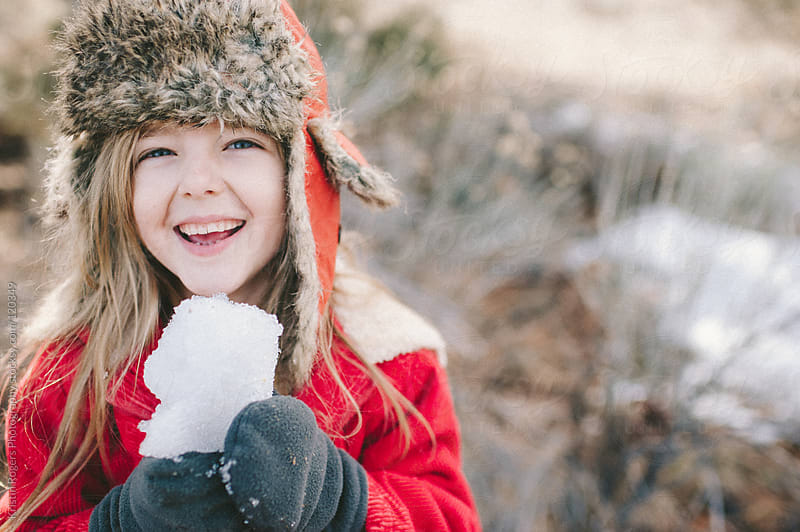 young girl laughing with snow in hands by Kristin Rogers Photography for Stocksy United