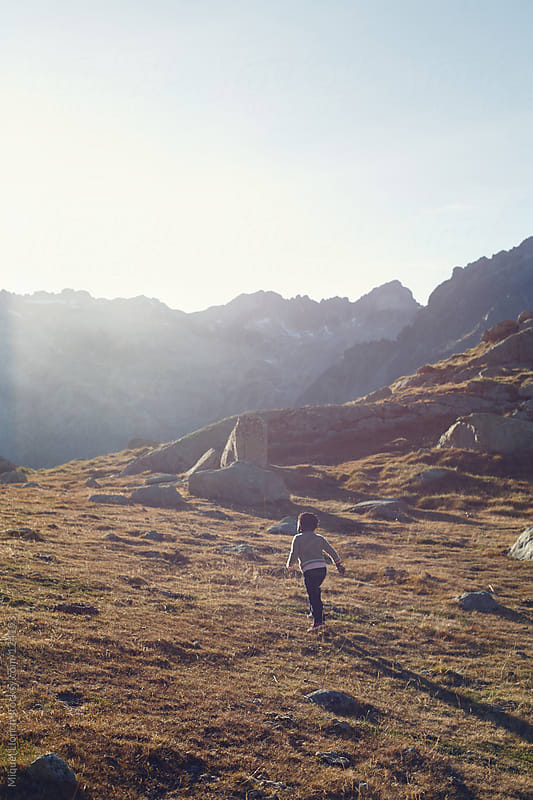 Little girl playing and enjoying the nature in the mountains by Miquel Llonch for Stocksy United