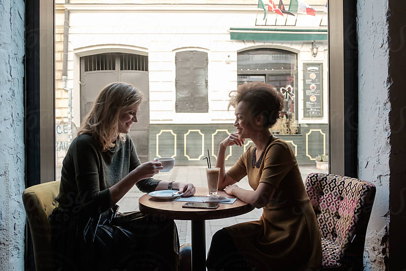 Two Female Friends Drinking Coffee at the Cafe by Brkati Krokodil for Stocksy United