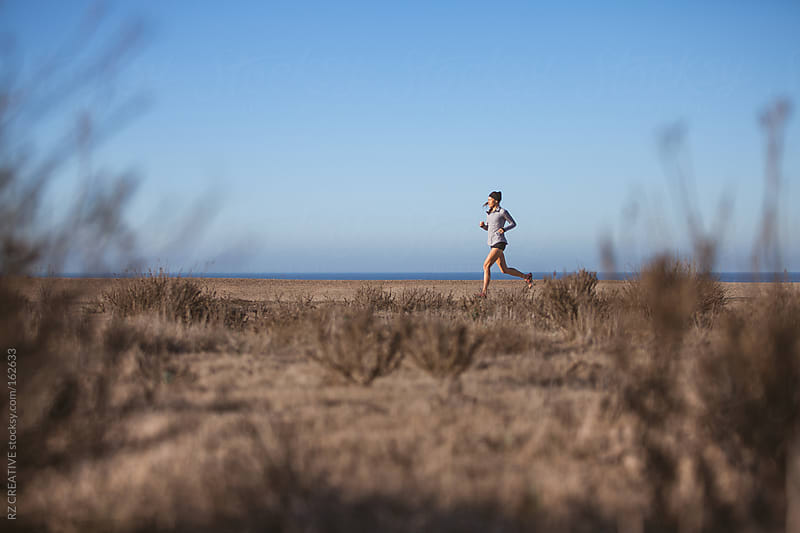 A woman in her mid-twenties running along a coastal trail.  by RZ CREATIVE for Stocksy United