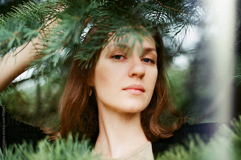 A film portrait of young beautiful woman standing between green leaves by Anna Malgina for Stocksy United