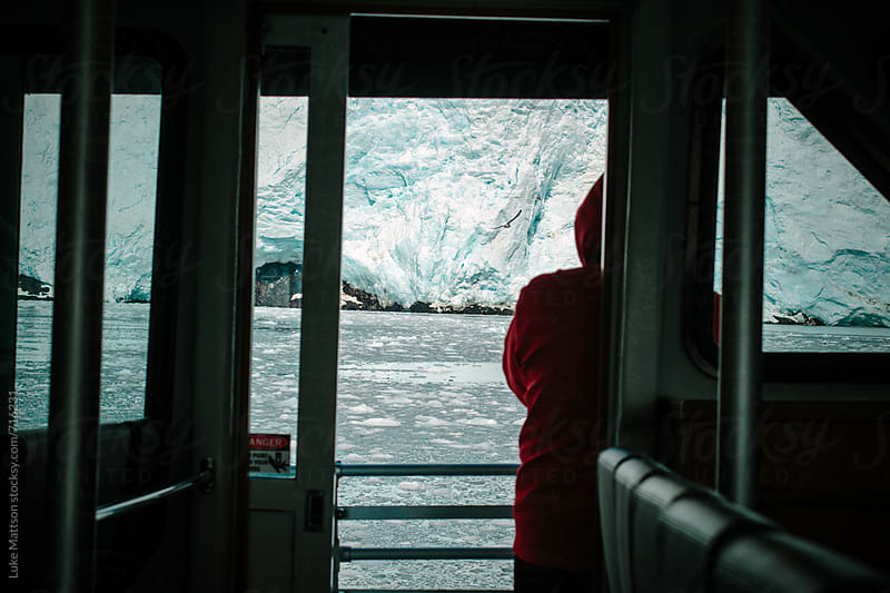 A Passenger Of A Glacier Cruise Ship Stands On The Port Side Deck Looking At The Glacier Face by Luke Mattson for Stocksy United