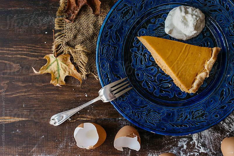 Pumpkin pie slice in a blue plate from above by Gabriel (Gabi) Bucataru for Stocksy United