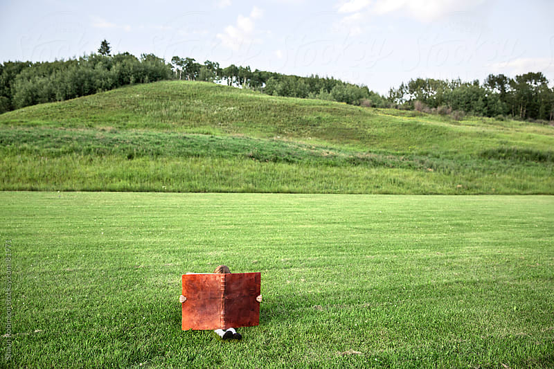 a girl sitting in a grass field with an oversized book by Shaun Robinson for Stocksy United