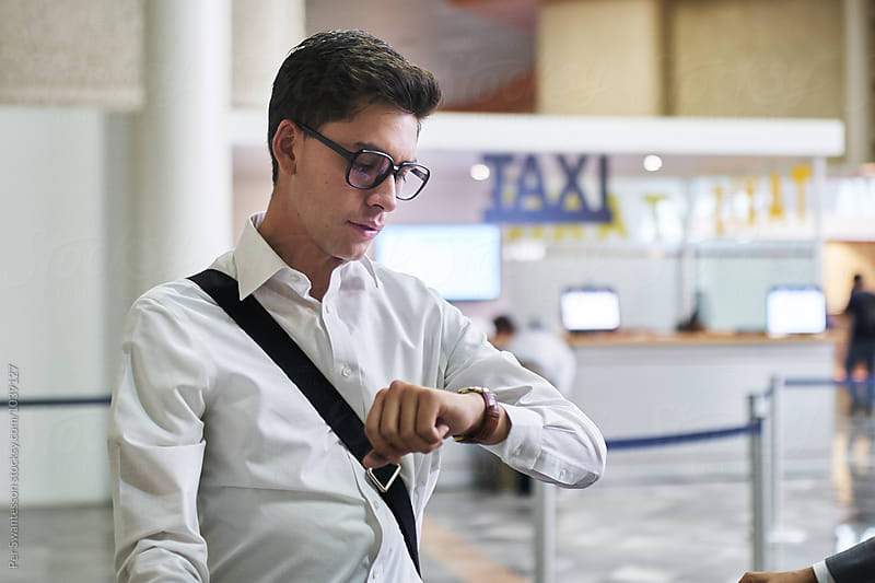 Young man waiting for transportation at airport by Per Swantesson for Stocksy United