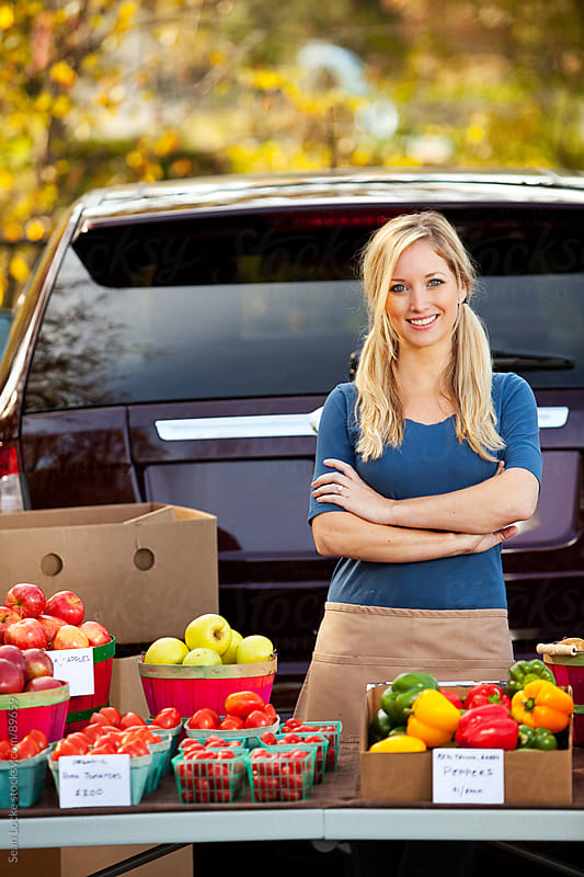 Farmer's Market: Cheerful Woman Selling at Farmer's Market by Sean Locke for Stocksy United