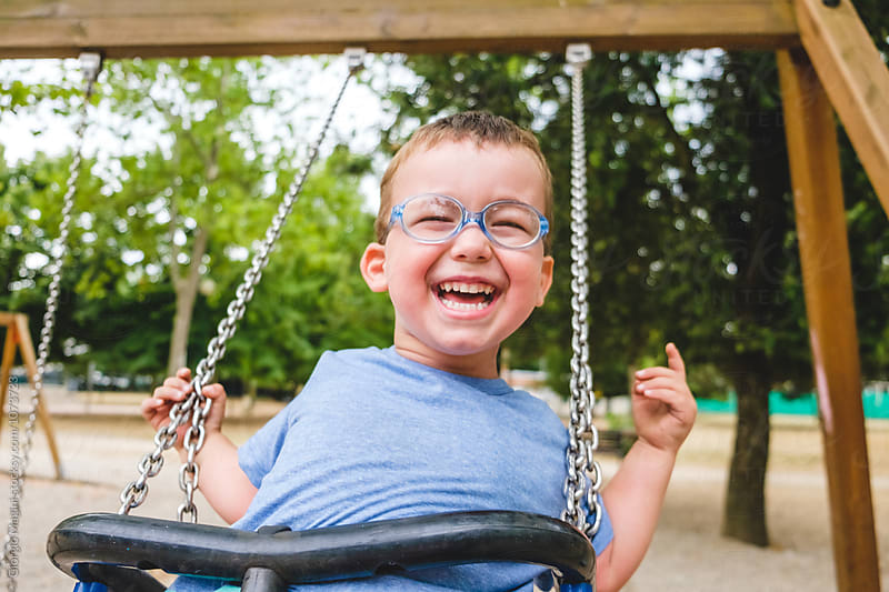 Happy Male Toddler Enjoying the Swing at the Playground by Giorgio Magini for Stocksy United