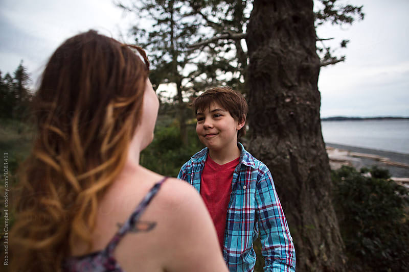 Mom and son spending time together outside in nature - talking by Rob and Julia Campbell for Stocksy United