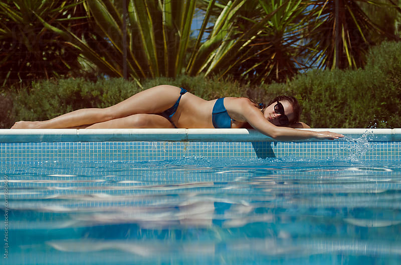 Sexy handsome woman sunbathing by the pool on hot summer day by Marija Anicic for Stocksy United