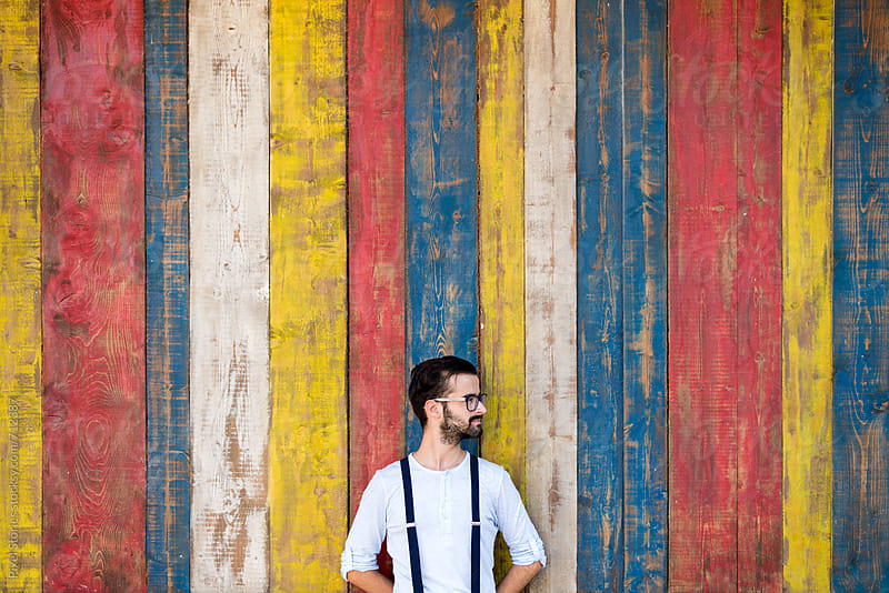 Young man leaning against colorful wooden background by Pixel Stories for Stocksy United