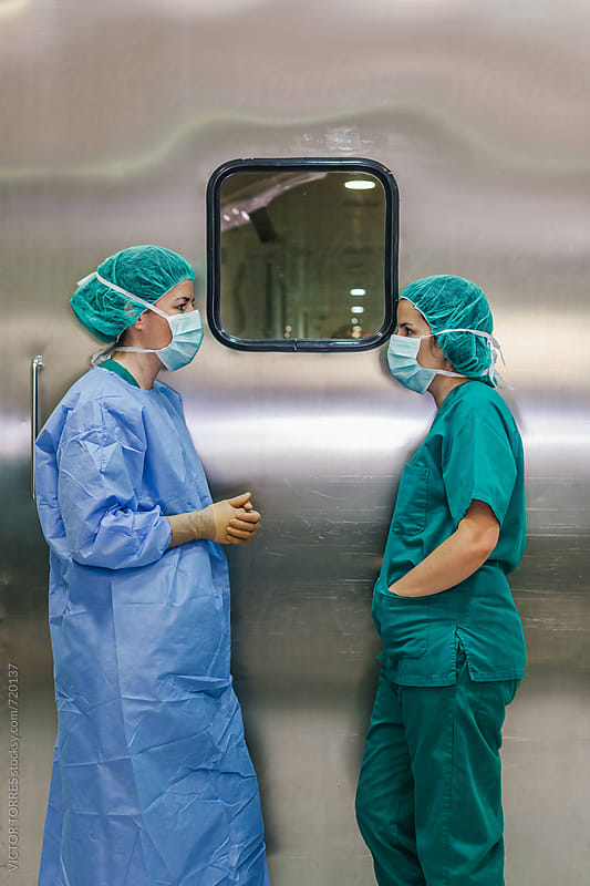 Surgeons Checking a List in an Operating Room by VICTOR TORRES for Stocksy United