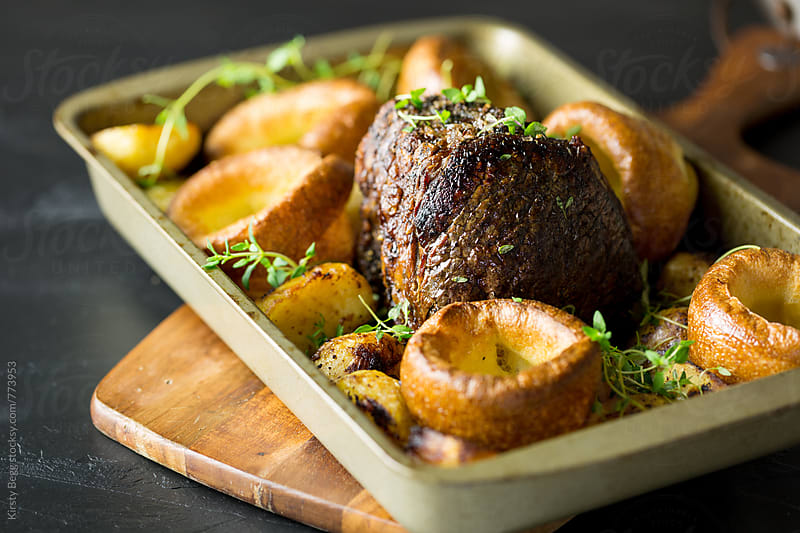Roast beef joint in roasting tray with Yorkshire pudding and potatoes by Kirsty Begg for Stocksy United
