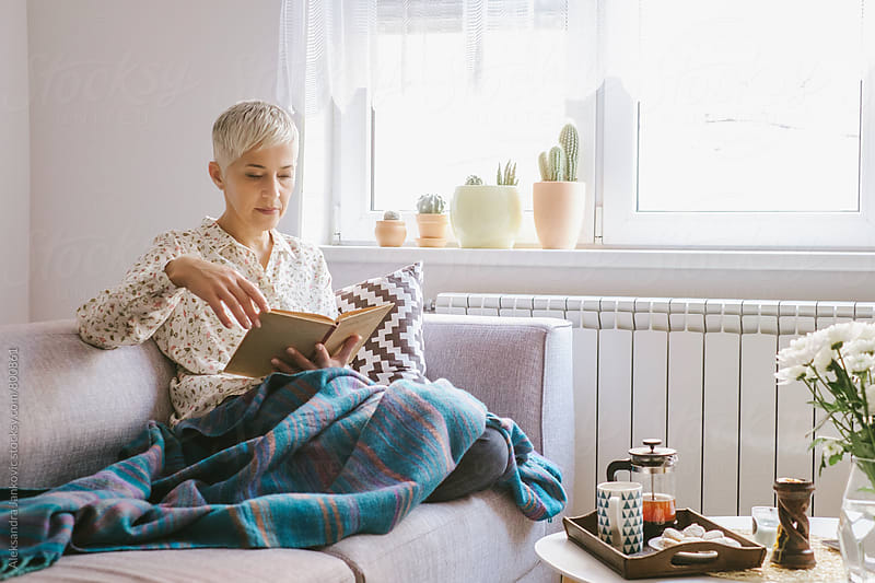 Senior Woman Relaxing at Home and Reading a Book by Aleksandra Jankovic for Stocksy United
