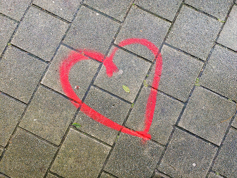 red heart painted on the street of pavement by Ivo de Bruijn for Stocksy United