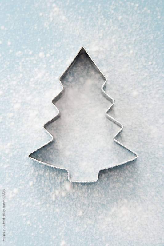 Christmas Tree Cookie cutter on blue background by Melanie Kintz for Stocksy United