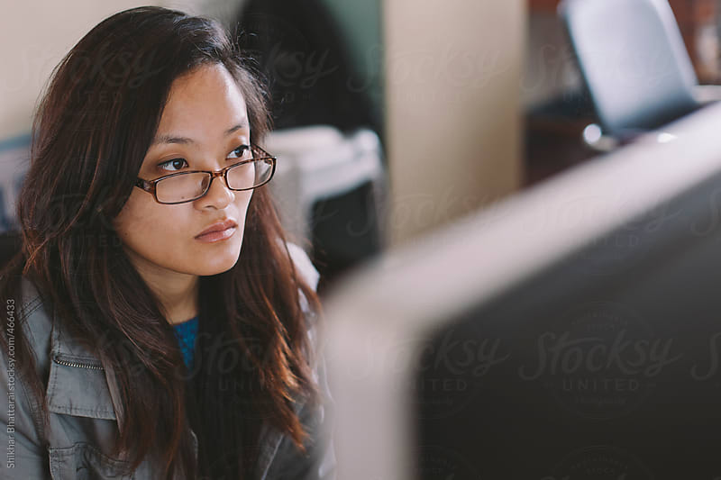 A young asian woman working on a computer. by Shikhar Bhattarai for Stocksy United