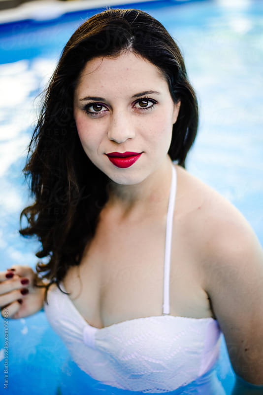 Young brunette with white swimsuit at the pool looking at the camera by María Barba for Stocksy United