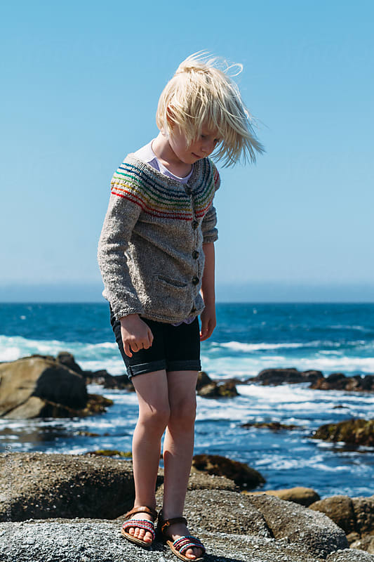 blonde child standing on shore by Jess Lewis for Stocksy United