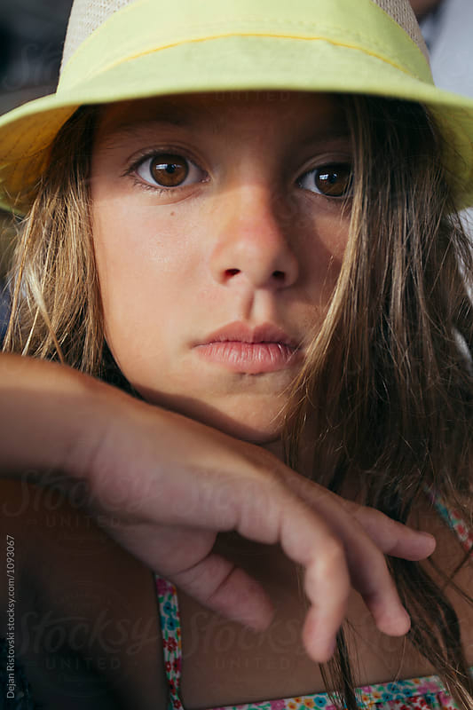 Summer portrait of a girl with hat and sunshine on her face. by Dejan Ristovski for Stocksy United