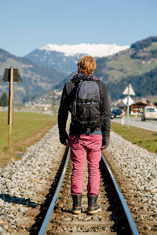 A man standing on a train track in the mountains by Ivo de Bruijn for Stocksy United