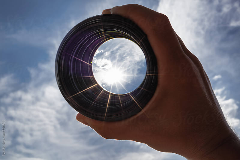 View through spyglass lens to the sun shining in the sky by Ilya for Stocksy United