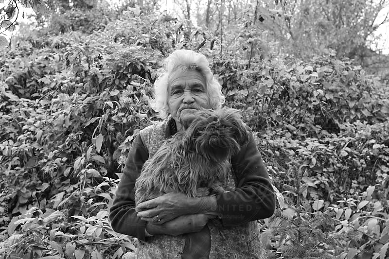 Old woman with her dog in the backyard  by VeaVea for Stocksy United