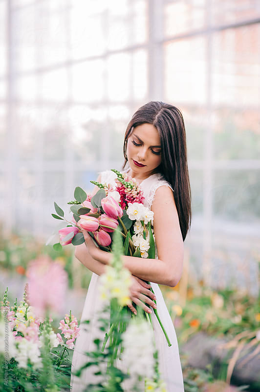Young woman in a white dress holding flowers bouquet by Adrian Cotiga for Stocksy United