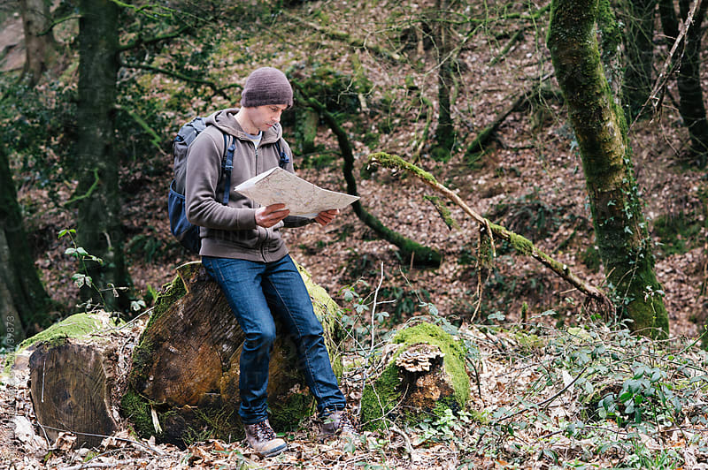 Man sitting in a wood reading a map by Suzi Marshall for Stocksy United