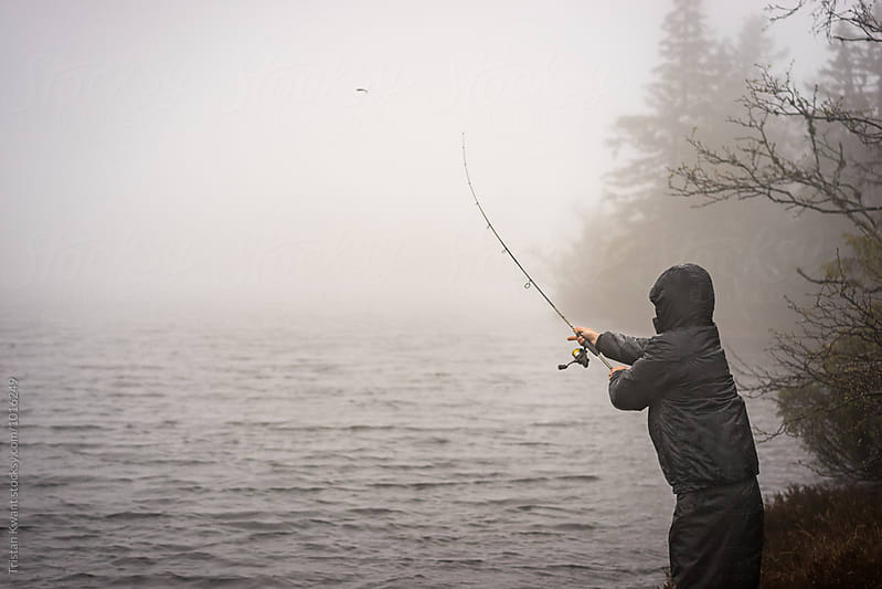 Man fishing in a mountain lake in bad weather. by Tristan Kwant for Stocksy United