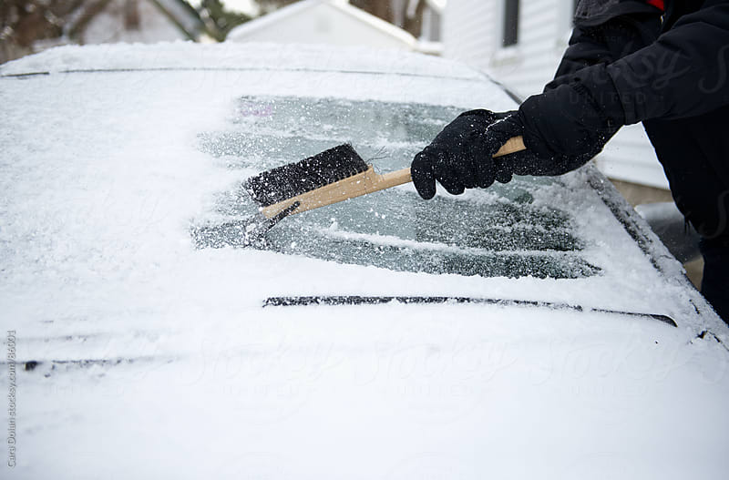 Man uses scraper to remove the snow and ice from the windshield of his car by Cara Dolan for Stocksy United