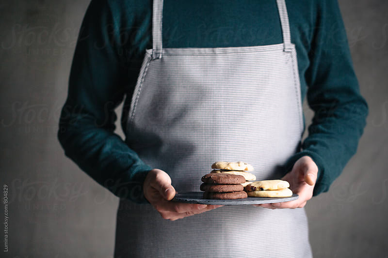 Man in an Apron Holding Cookies by Lumina for Stocksy United
