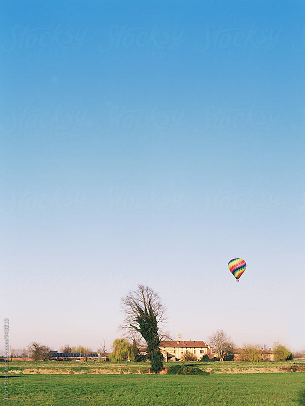 Hot air balloon flying upon farm in italian countryside by Laura Stolfi for Stocksy United