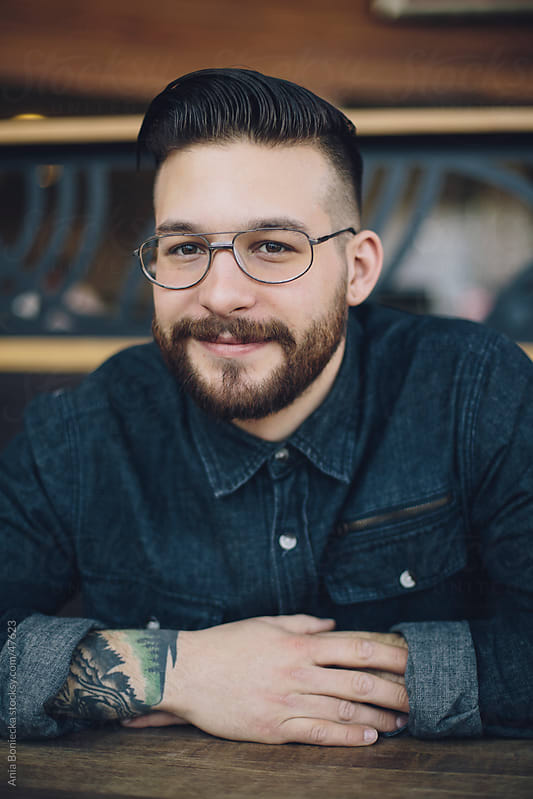Portrait of a man with a beard and glasses smiling by Ania Boniecka for Stocksy United