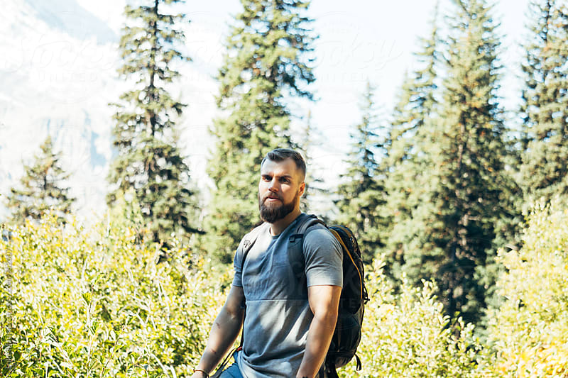 Stoic Blond Bearded Man Wearing Backpack On Forest Hike by Luke Mattson for Stocksy United