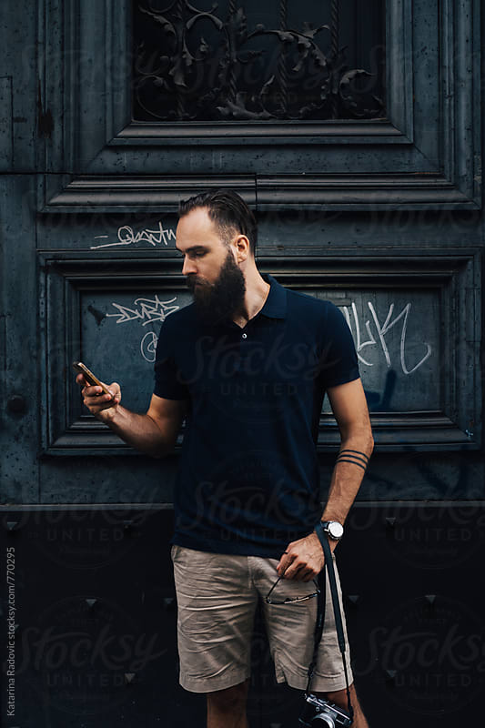 Portrait of a Handsome Bearded Man Using His Phone by Katarina Radovic for Stocksy United